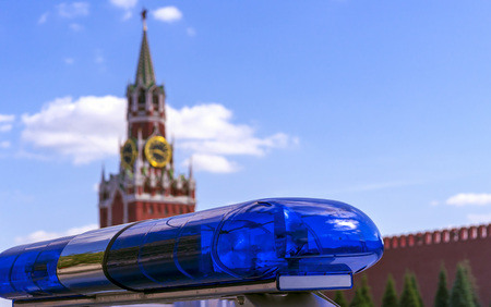 Blue police siren against the background of the Kremlin in Moscow. Police flasher on the background of the Spasskaya Tower of the Moscow Kremlin.