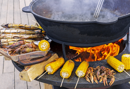Fish, crayfish and corn are grilled on a round grill.