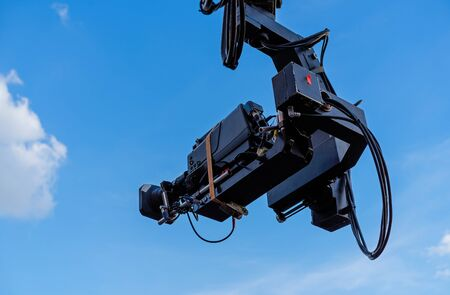 TV camera on the operator crane. Camcorder on a background of blue sky.