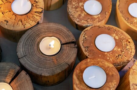 Burning candles in wooden candlesticks. Bright warm glow from candle flames.