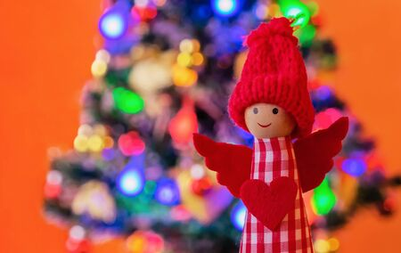 Angel in a red knitted hat on the background of the Christmas tree. New Year and Christmas background.