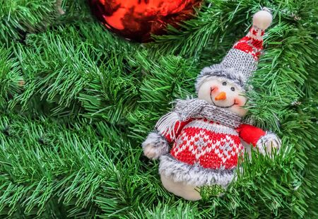 Snowman dressed in a knitted sweater and hat on the Christmas tree.