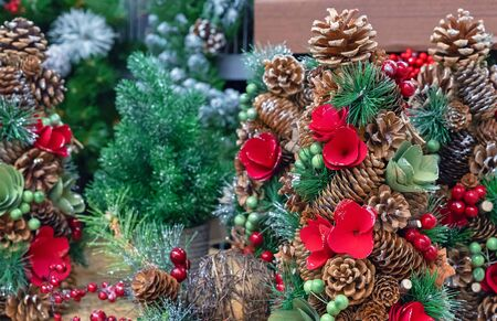 Christmas decorations with pine cones, red berries and flowers.