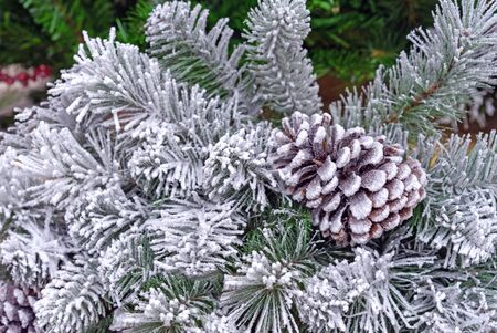 Snow-covered Christmas tree with a pine cone. New Years decor.