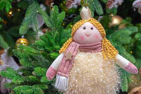 Doll princess with a crown on the background of the Christmas tree.