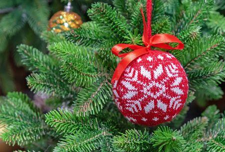 Red woolen Christmas ball with a Scandinavian ornament on a green spruce. Zdjęcie Seryjne