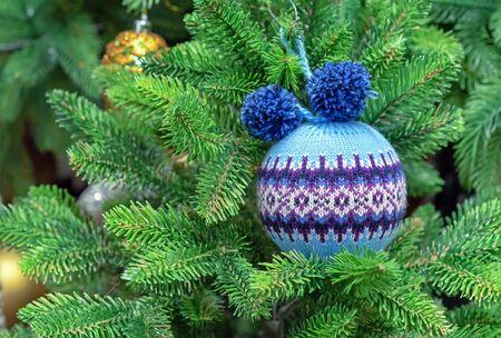 Blue woolen Christmas ball with a Scandinavian ornament on a green spruce.