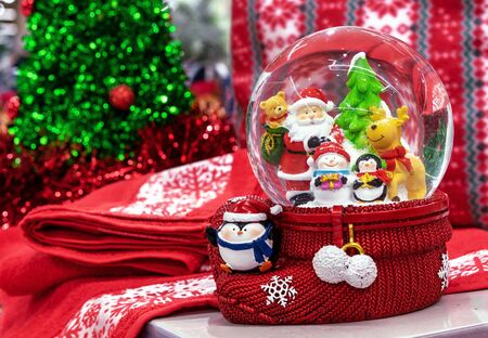 Glass snow globe with Santa Claus, deer, penguin, christmas tree and snowman inside.