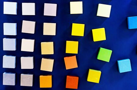 Colored wooden cubes on a blue background. The concept of a palette of paints for wood.