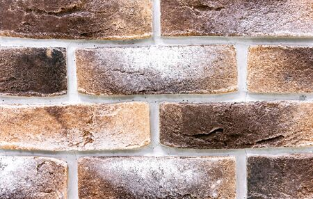 Decorative brick wall from of beige and brown bricks. Background and texture of brickwork. Imagens