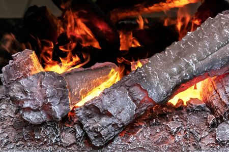 Firewood and fire in an artificial fireplace. Stock fotó