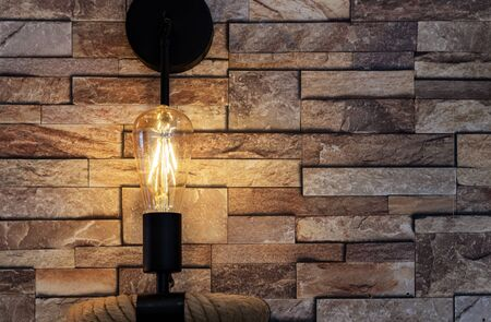 Lightbulb in vintage style on a stone wall background. Edison lamp in the loft interior.