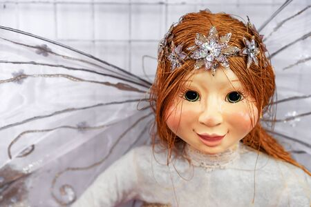 Doll with red hair and a diadem. Realistic doll with dragonfly wings.