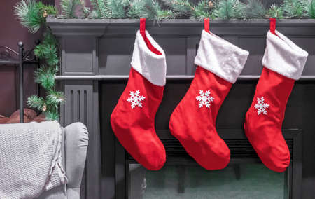 Three red Christmas stockings for gifts over the fireplace in the living room.