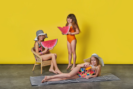girls in bathing suits and hats on a yellow background