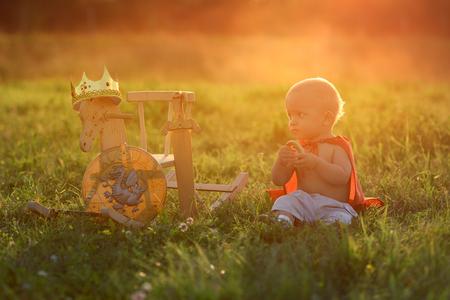小さな少年王馬のおもちゃ屋外光が日没で座っています。王子は食べる草の上で休憩します。 写真素材