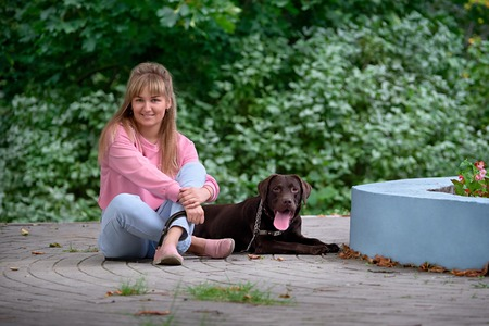 pillowy: blonde girl smiling with dog Labrador. Labrador lying next