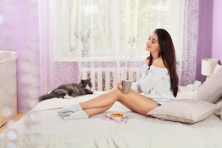 Young beautiful brunette woman with cup of coffee sitting home on the bed by the window. Girl relaxing in bed.