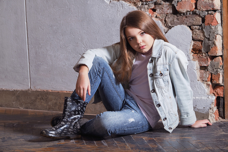 Portrait fashion kid girl. child fashion concept. girl near wall sits floor. Banque d'images