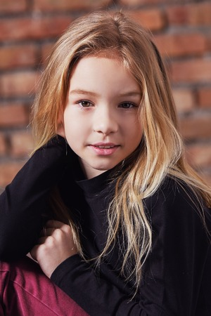 closeup portrait fashion kid girl. Stylish young model child blond hair. pretty beauty female face small child. fashion concept. models tests caucasian appearance. Stock Photo