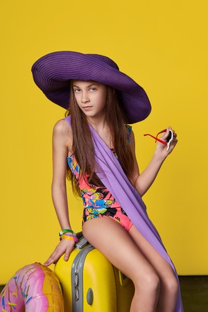 Attractive girl teenager 11 years in swimsuit, hat, holds sunglasses in his hand. Concept summer, travel. Portrait cute young beauty woman on a bright yellow background studio. Standard-Bild