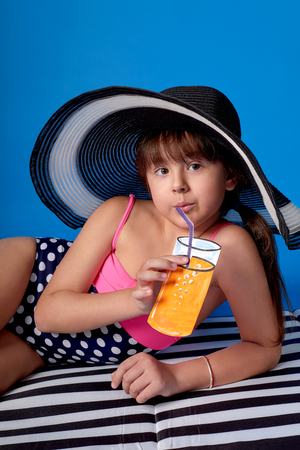 Studio summer portrait young child woman looking at camera. Fashion beauty little girl swimsuit,beach hat. Beautiful teenager girl loves summertime, lovely rest beach, summer vacation, travel.