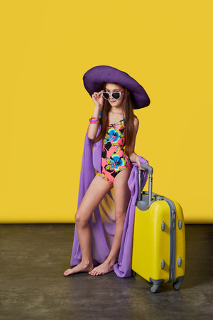 Attractive girl teenager 11 years in swimsuit, hat, sunglasses, suitcase. Stunning girl model in a colorful bikini and pareo posing on a bright yellow background. Studio shot. Concept summer, travel.