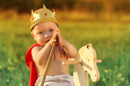 Portrait little child prince.Adorable knight baby 1 years in costume hero,king,warrior on head golden crown,hand holds sword.Beautiful face kid,background lawn,nature.Young prince resting summer day.