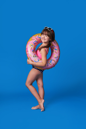 Beach Vacation concept.Isolated on Blue background. Pretty child model cute smile.Fashion beauty little girl swimsuit,inflatable ring.Advertising rest beach,summer vacation,travel.