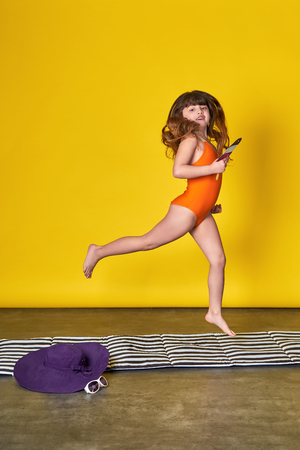 Young little girl jumping up fun on bright yellow clothes for swimming