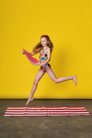 Concept summer,vacation,travel.Young caucasian girl jumping up,bright yellow background.Fashion sunny photo studio.Active child teenager in colorful swimsuit suit loves summertime,lovely rest beach. Stock Photo