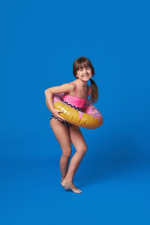 Beach Vacation concept.Happy cute little girl smiling holding swimming ring on body.Pretty fashion child dressed in swimsuit fun poses.Beautifu kid teenager loves summertime.Isolated blue background. Stock Photo