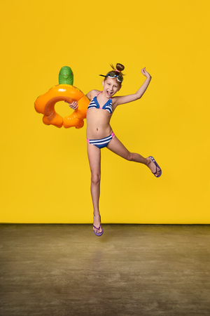 Beach Vacation concept.Funny girl teenager in bathing suit jumping up fun.Fashion child in movement smiles,emotion joy,happy.Full length, yellow background.Advertising rest, summertime, travel.