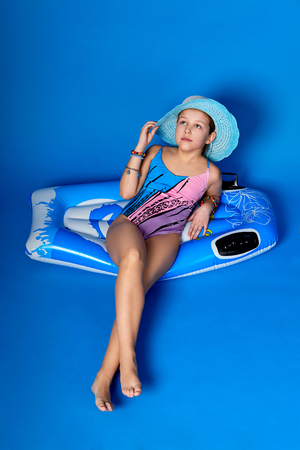 Young girl in swimsuit,blue hat resting on inflatable mattress for swimming. Concept summer break,vacation,travel,resort.Little lady girl in bathing suit for beach relaxing isolated blue background.