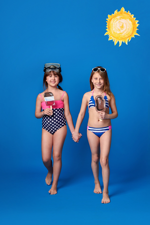 Studio summer portrait young 2 girls looking at camera. Beach vacation concept. Girlfriends wear swimsuits,sunbathing,swimming in water, warm,sunny day.Fashion kids go together, holding hands.
