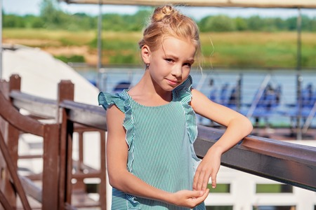 Portrait elegant young girl of 9-11 years outdoors, leaning her elbows on the railing. Cute child blonde smiling, sunny summer day resting on pier. Fashion kid concept. striped dress, marine style.