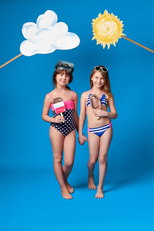 Studio summer portrait full length young girls friends.Beautiful children posing in swimsuits, slim body,holding ice cream painted.Fashion kids go together,holding hands.Blue background, studio.