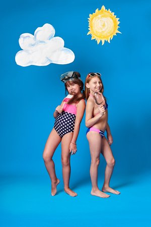 Concept summer,beach.Children girls model colorful swimsuit posing,holding hand ice cream,on head mask diving. Caucasian kids,blue background with sun,cloud in studio. Advertising,sea recreation.