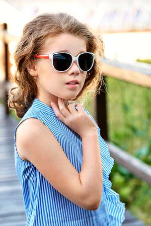 c6d2895791e5 Elegant child portrait. Little girl model wearing summer cool clothing,  sunglasses. Marine style