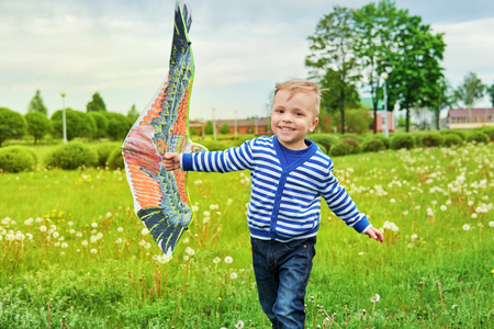 Happy little boy smiling running across park with kite bird flying. Child fun playing outdoors on summer or spring day.Joyful childhood. Lifestyle. Attractive kid actively recreation on nature, grass.