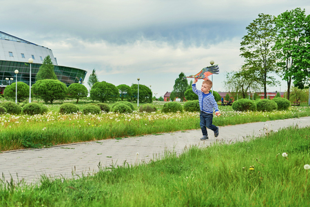Little boy running across park with kite flying. Caucasian child playing on spring day. Joyful childhood. Lifestyle kid actively recreation .Copy space for text. Summer day,outdoors, green grass. Foto de archivo