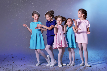 Group happy children in celebratory clothes for lady girls. Concept fashion, holiday, christmas, new year, x-mas, winter. Five kids in beautiful dresses enjoying snow on eve new year. Studio shot. Foto de archivo