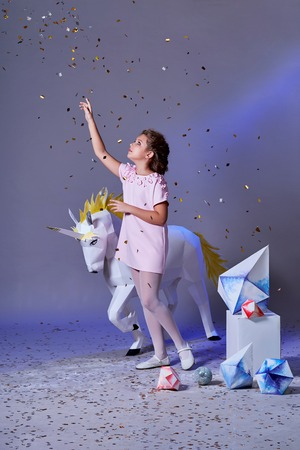 Holidays, christmas, new year, x-mas,concept. Little girl in elegance dress for party pointing finger on glitter confetti. Fashion lady teenage poses full-length in studio, gray purple background.