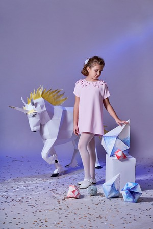 Young kid girl in elegance dress pink. Concept winter, eve, Christmas, new year. Fashion lady teenage poses for childrens clothing catalog. White big unicorn origami near. Studio purple background. Foto de archivo