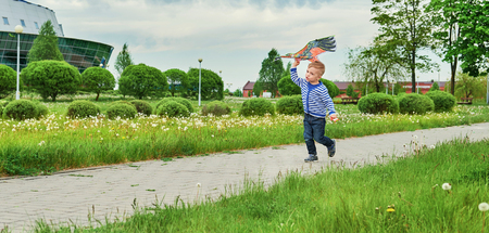 Little boy running across park with kite flying toy. Caucasian child playing on spring day. Joyful Lifestyle kid actively recreation on street.Summer day,outdoors.Copy space for text,blank background.