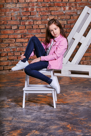Confident child girl sitting fashion pose on chair. Stylish model child. Beautiful glamorous kid teenagerbrunette advertises ,casual,urban,street,youth style. clothes. Studio shot, loft interior. Foto de archivo