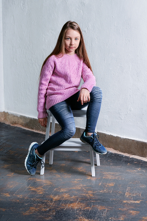 Confident child girl sitting fashion pose on chair,concrete white background. Stylish model in pink sweater. Beautiful glamorous kid teenager,casual,urban youth style,clothes. Studio shot. Foto de archivo
