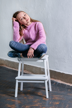 Stylish child girl sitting fashion pose on chair. Beautiful glamorous kid teenagerbrunette advertises ,casual,urban,street,youth style. clothes. Studio shot, loft interior.