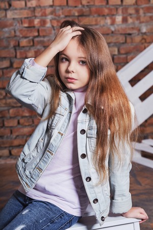 Portrait little fashion kid.Stylish hipster girl child wearing denim jacket,jeans clothes,posing against rough brick wall. looks confident,defiant.Beautiful face caucasian Childrens,fashion concept. Foto de archivo