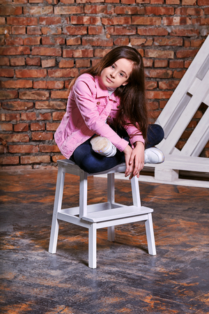 Stylish model child. Portrait girl kid teenager pose sitting on chair. Beautiful brunette advertises casual clothes, youth style trend. Studio shot, loft interior. Foto de archivo